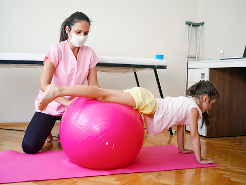 Beautiful little girl on physical therapy stretching her back while leaning on ball