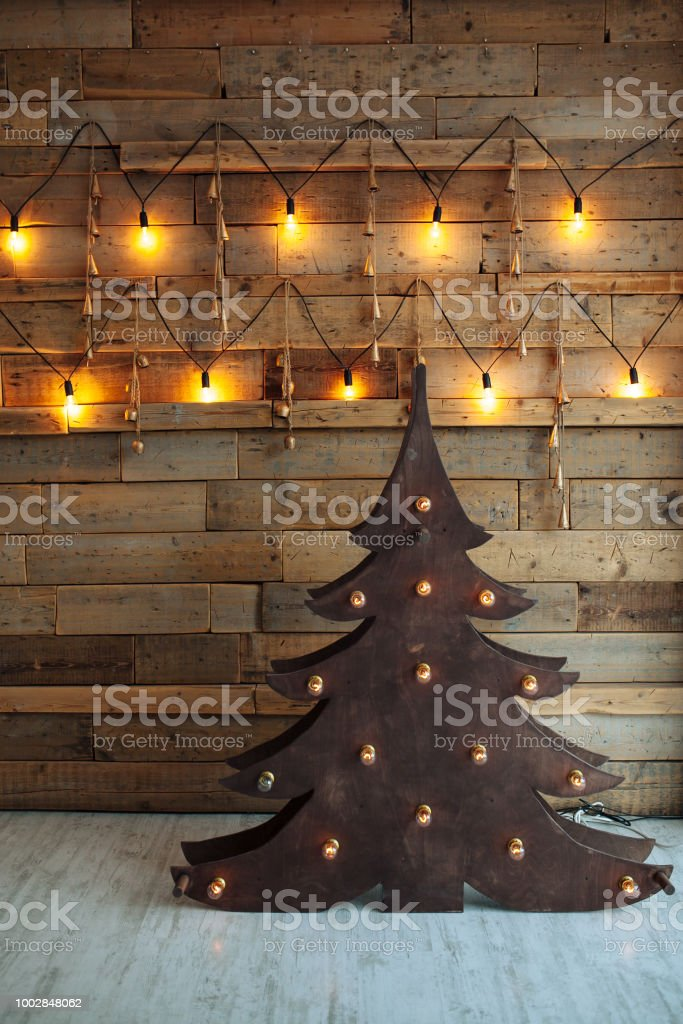 Alternative wooden christmas tree. A handmade New Year tree with light bulb on the floor on wooden background. Loft interior. Copy space stock photo