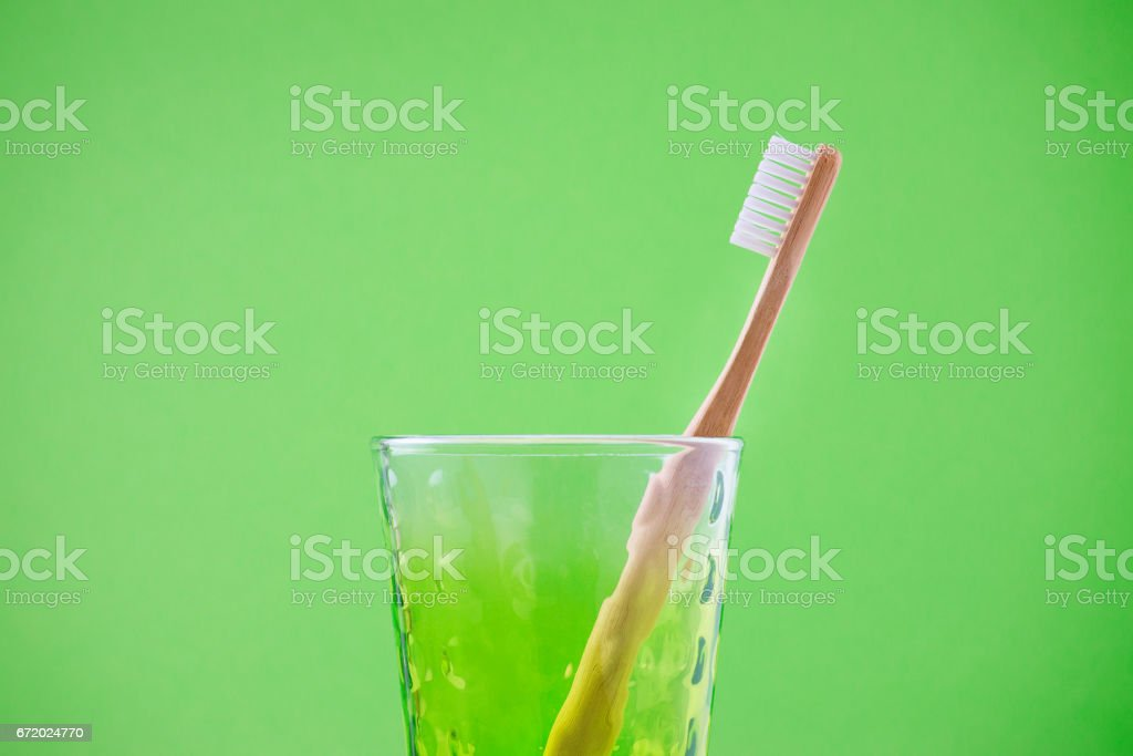 alternative wooden toothbrush in a glass on green background, horisontal stock photo