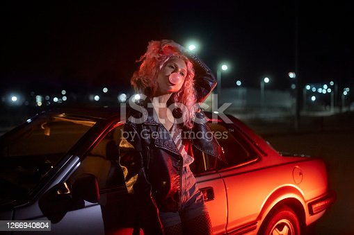Alternative young hipster girl leaning on car with bubble gum at night