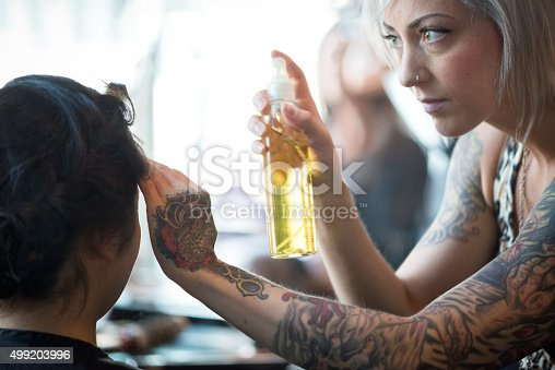 istock Alternative Young Woman Hair Stylist Finishing Client's Hair with Hairspray 499203996