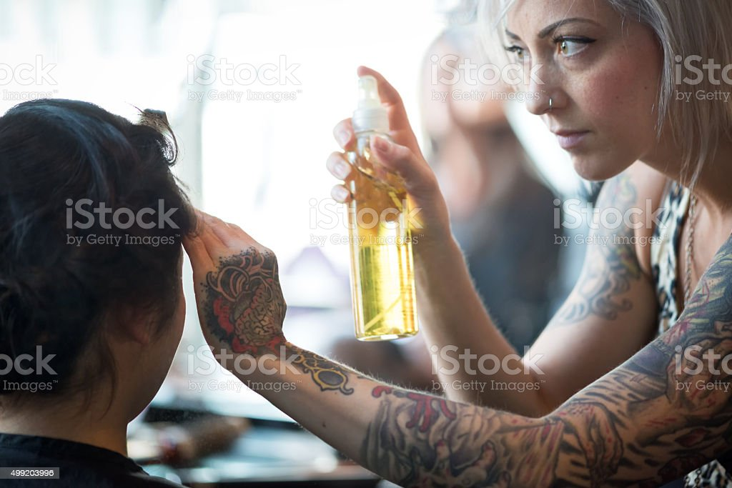 Alternative Young Woman Hair Stylist Finishing Client's Hair with Hairspray stock photo