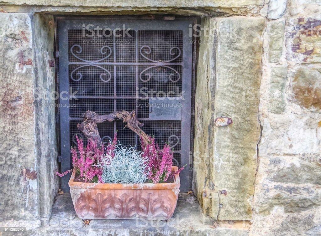 Altes Fenster altes fenster in natursteinmauer mit terrakottapflanztrog stock