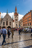 Munich, Germany - September 7th, 2018: Tourists and locals stroll in Marienplatz, the town square in historic center. On background the Altes Rathaus (Old Town Hall) XIX century neo-Gothic style palace and the Heiliggeistkirche (Church of the Holy Spirit). Marienplatz is the most important town square of Munich and is a pedestrian zone.