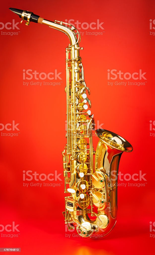 Alto saxophone in full length on red background stock photo