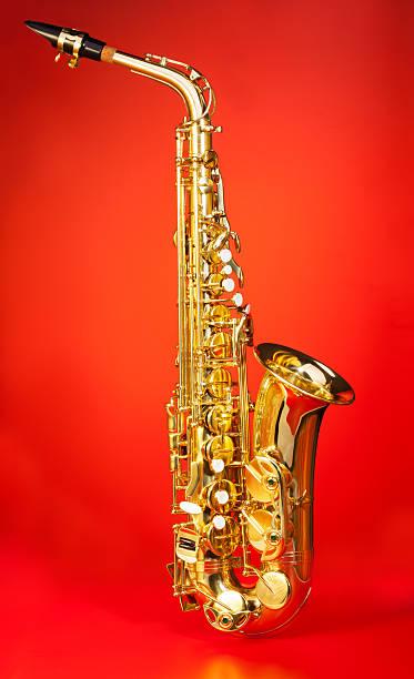 altsaxophon in voller länge auf rotem hintergrund - altsaxophon stock-fotos und bilder