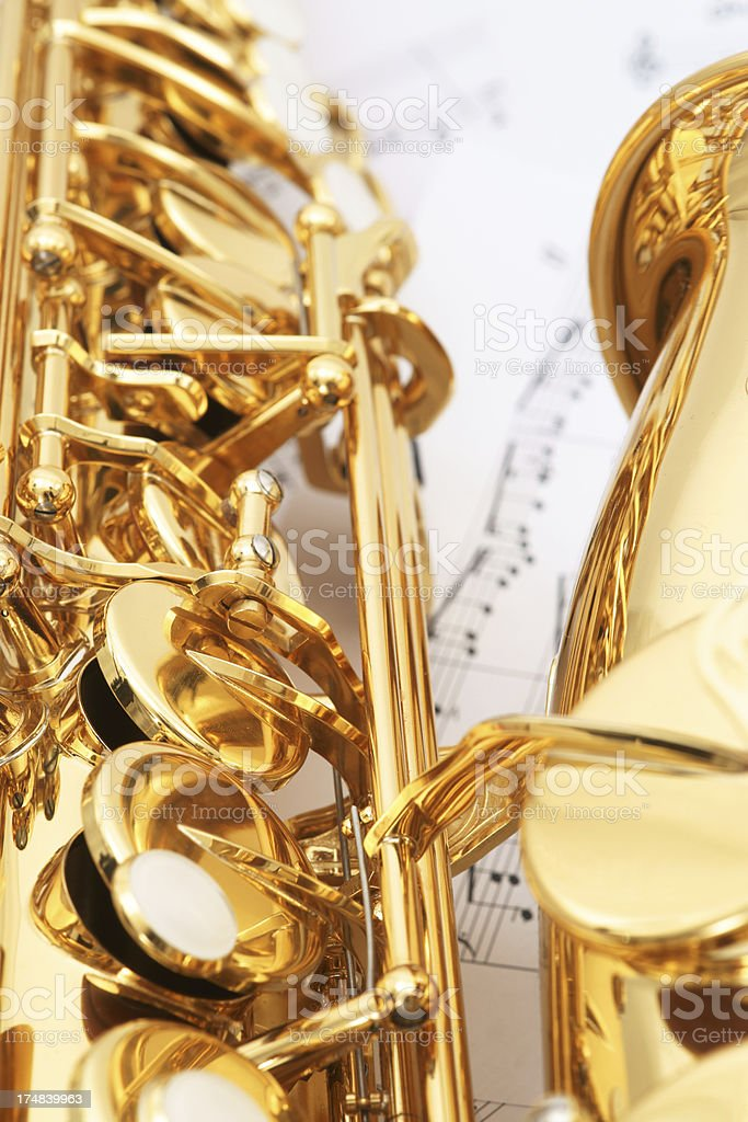 Alto saxophone with music sheets in background royalty-free stock photo