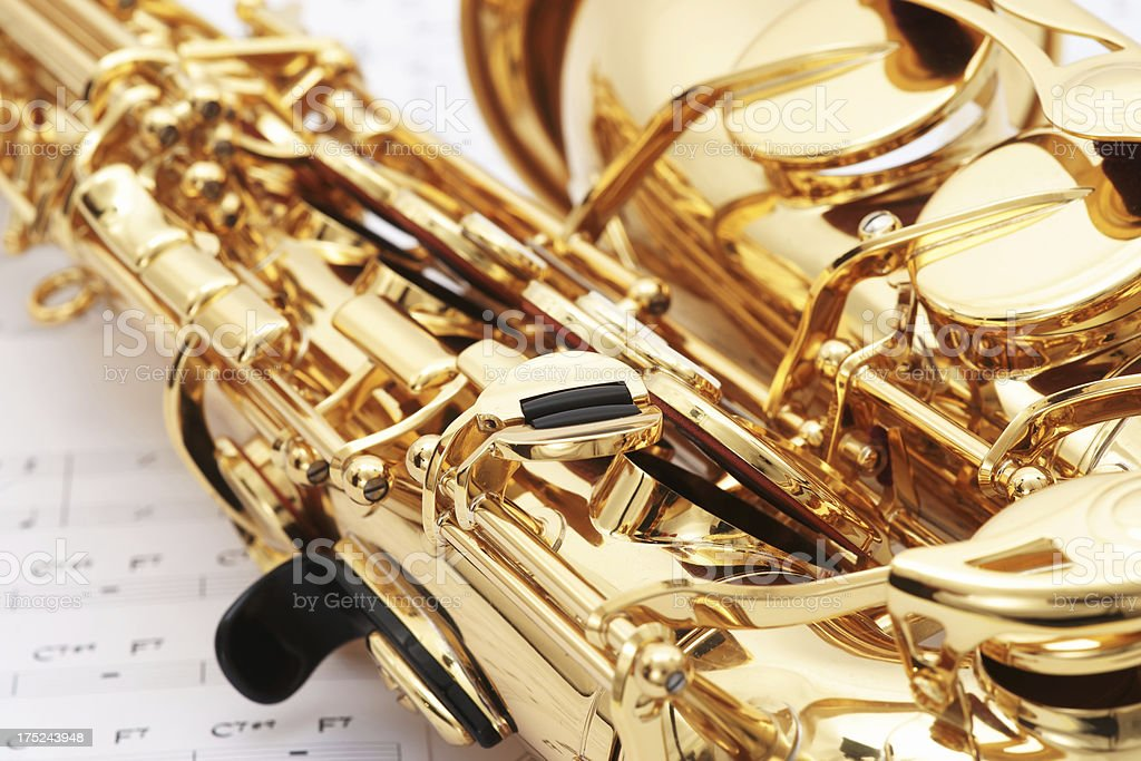 Alto Saxophone With Music Sheets In Background Stock Photo
