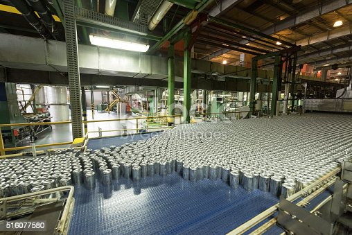 Metal drinks cans on production line in manufacturing plant. Industrial building interior with abundance of aluminium cans.