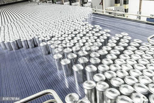 Blurred motion of metal drinks cans being processed in industrial factory. Production line with abundance of containers moving at speed.