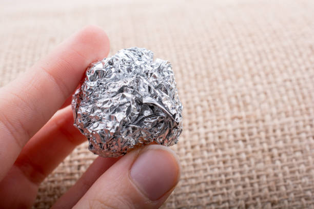 Aluminium foil in the shape of a sphere on  textured background stock photo