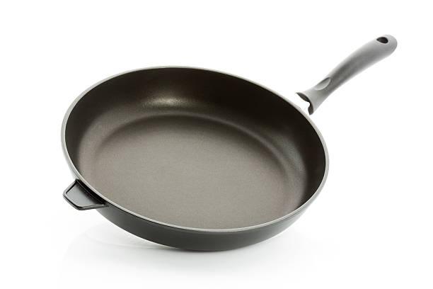 Aluminium fry pan isolated against white background stock photo