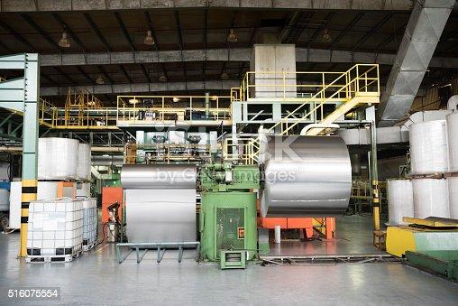 Industrial machines in factory with aluminium rolls. Specialist equipment for processing aluminium inside industrial building.