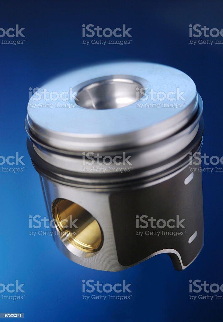 Aluminium motor piston, on blue background, close-up royalty-free stock photo