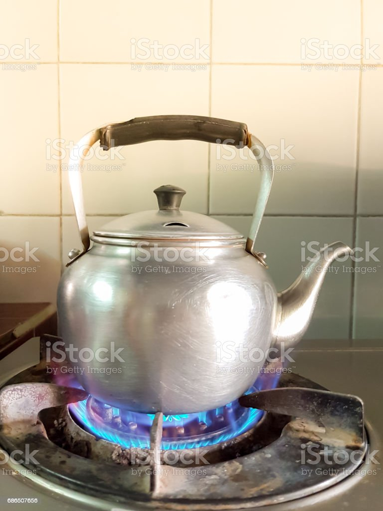 aluminium teapot boil on the old gas stove with flame royaltyfri bildbanksbilder