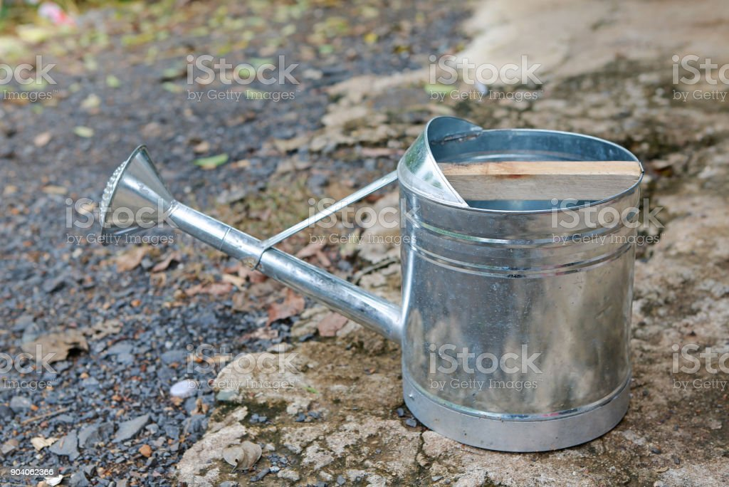 Aluminium watering dipper place on the ground. stock photo