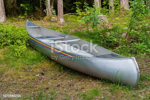 aluminum canoe lying in a forest in Sweden
