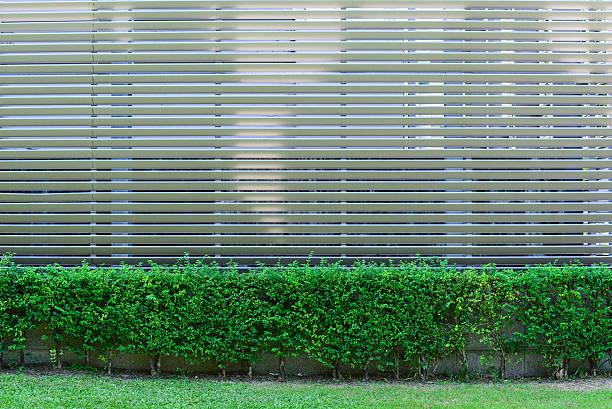 aluminium zaun mit hübschen pflanzen umgeben fabrik. - alu zaun stock-fotos und bilder