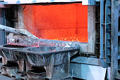 skimming melted aluminum for removing the dross before casting. Aluminum foundry works showing an open furnace