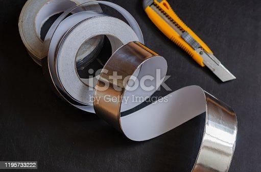 istock Aluminum insulation tape on a dark table. 1195733222