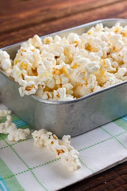 aluminum plate full of salty popcorn on towel - zout smaakstof stockfoto's en -beelden