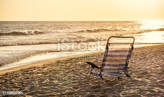Aluminum striped deckchair at ocean sandy beach with sunset light and vintage tone