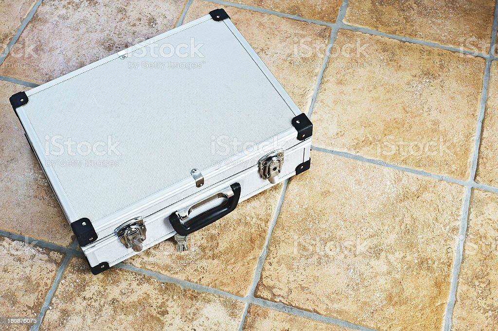 Aluminum suitcase on floor royalty-free stock photo