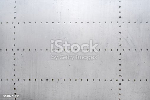 Aluminum surface of the aircraft fuselage. Smooth rows of rivets, there are scratches, dirt.