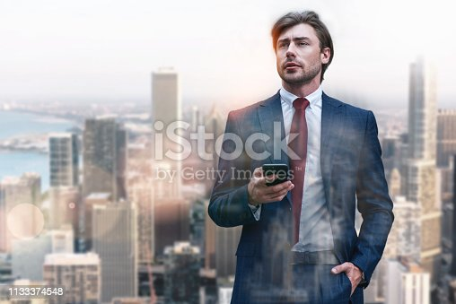 istock Always available. Handsome and stylish businessman in classic wear using his smart phone while standing against of cityscape background 1133374548