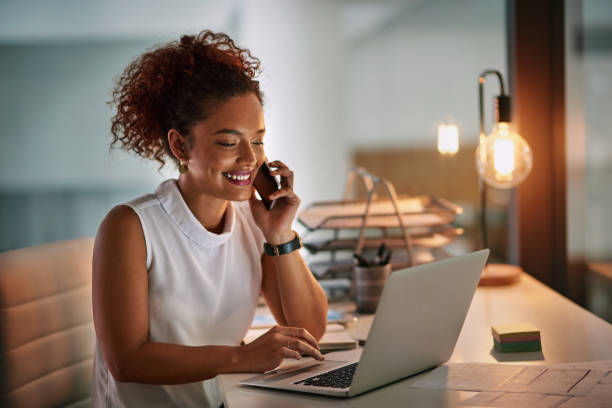 Always be ready when business comes calling Shot of a cheerful young businesswoman taking a phone call while working late in her office business laptop stock pictures, royalty-free photos & images