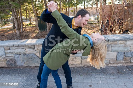 Happy young Caucasian couple spontaneously dancing in a public park on a sunny spring day. They are laughing as the young man dips the blonde young woman backwards.