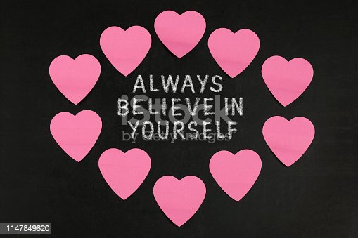 Paper Heart with text  Always believe in yourself on blackboard
