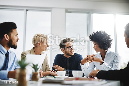 Cropped shot of a diverse group of businesspeople sitting together and having a meeting in the office