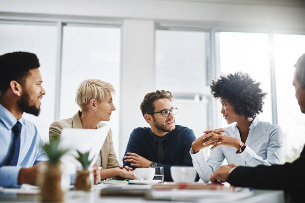 Always brainstorming Cropped shot of a diverse group of businesspeople sitting together and having a meeting in the office collaboration stock pictures, royalty-free photos & images