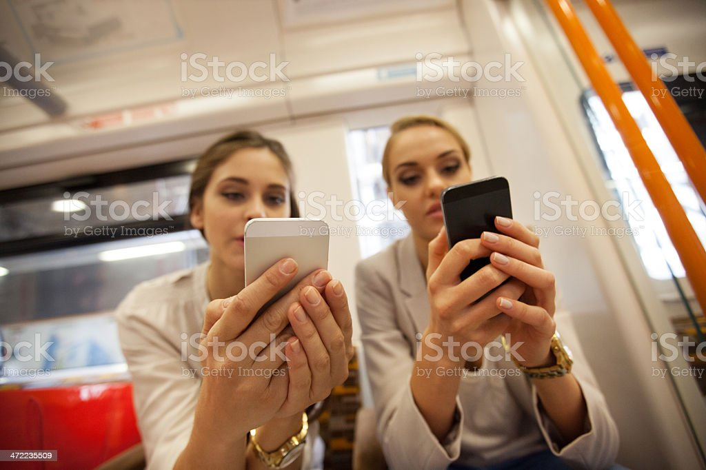Always connected Two young women sitting in a London overground train and using their smart phones. Close up on human hands. 20-24 Years Stock Photo
