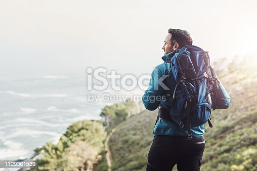 Rearview shot of a middle aged man hiking in the mountains