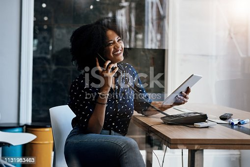 Shot of a young female designer making a phone call while holding a digital tablet at her office desk
