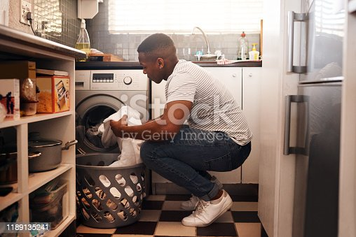 Shot of a man doing the laundry at home
