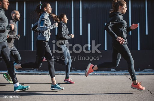 Young men and women running on city streets. They are wearing sport clothing.