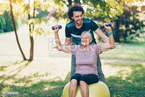 Young sportsman training a senior woman outdoors in the park