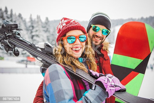 Couple on vinter vacation at mountain. Holding skis and preparing for skiing. Mountain is coverd with snow.