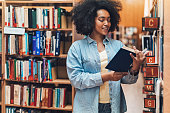 Young African ethnicity woman searching books in a library