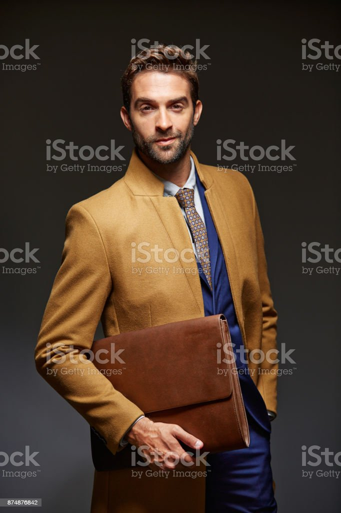 Studio portrait of a handsome young businessman posing against a dark...