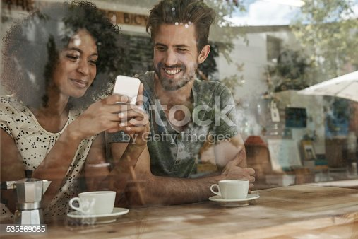 Shot of two friends looking at something on a cellphone, seen through glass