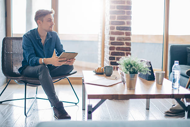 Always inspired in this place Young man using a laptop and talking with other inspiring and creative people.. Sitting in modern living room and working form home. bachelor stock pictures, royalty-free photos & images