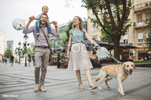 Family with one child outdoors on city street. Father carry son on piggyback, they enjoy in walk with their dog at summer.