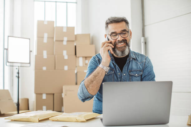 Always keep contact with customer Bearded men working on packaging and online delivery in home office business. He talking on phone with customer market vendor stock pictures, royalty-free photos & images