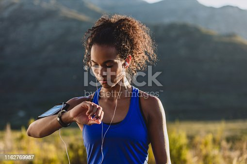 Cropped shot of a woman checking her wristwatch while out for a run
