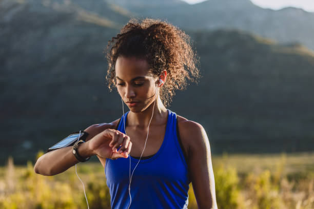 Always keep track of your process Cropped shot of a woman checking her wristwatch while out for a run fitness tracker stock pictures, royalty-free photos & images