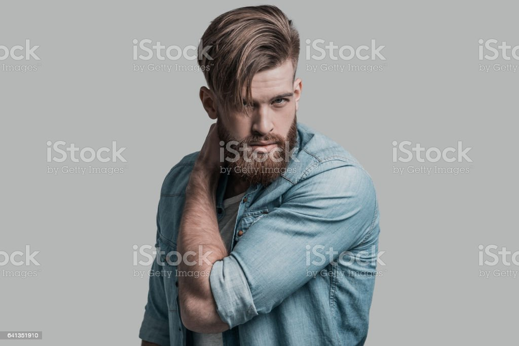 Always looks perfect. Handsome man looking at camera and holding hand on his neck while standing against grey background Adult Stock Photo
